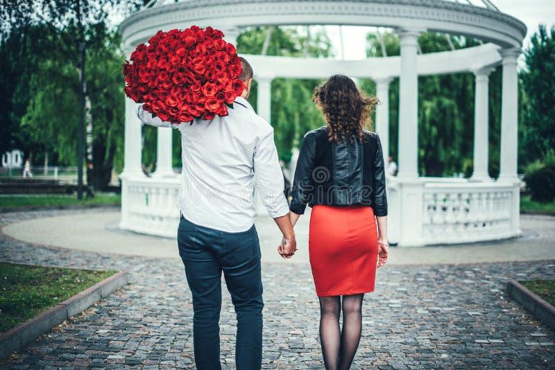 年轻夫妇在握手的公园 免版税库存照片