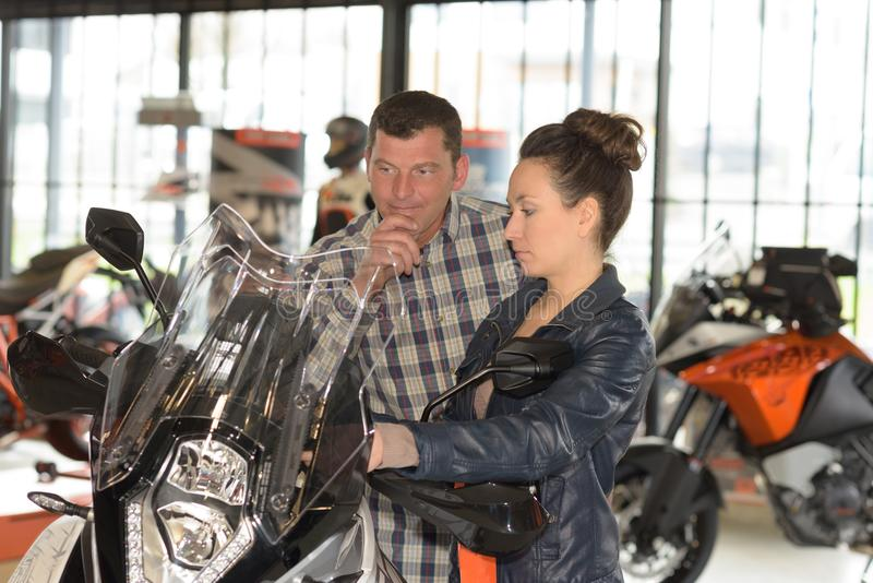 夫妇在摩托车陈列室里 免版税库存图片