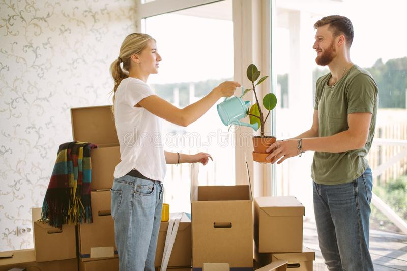 夫妇在新的家打开箱子 给花的妇女她的丈夫 免版税库存照片