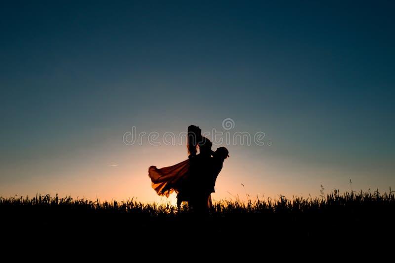 夫妇在日落的剪影跳舞 库存照片