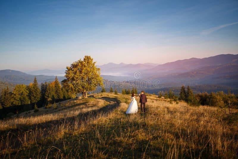 夫妇在日落的旅行山 蜜月 库存图片