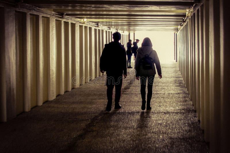 夫妇在有一个小组的地下过道走女孩在入口 免版税库存图片