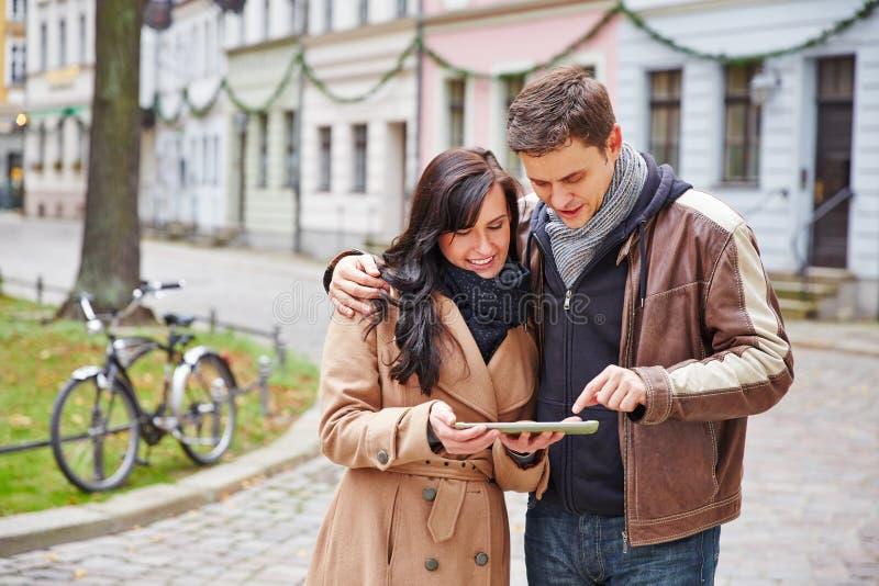夫妇在有片剂计算机的城市 免版税库存图片