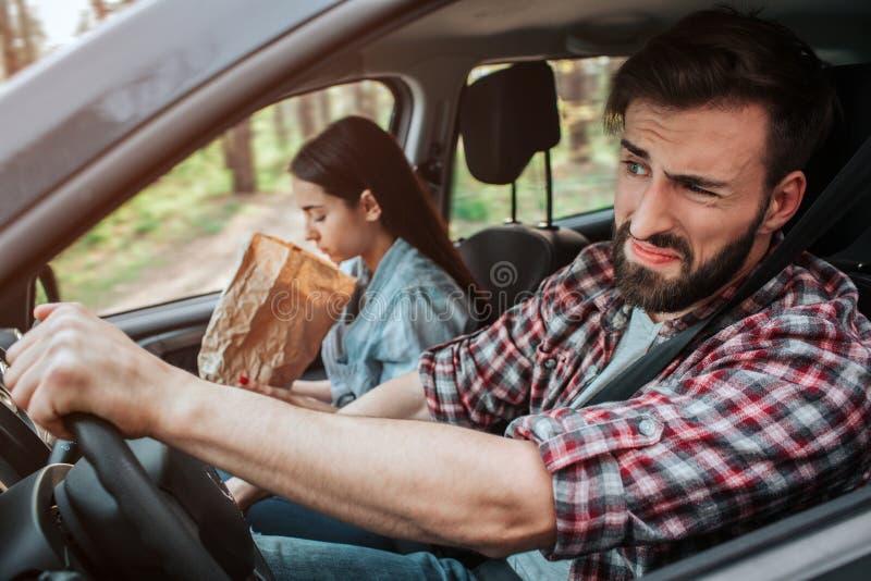 夫妇在汽车驾驶 女孩感到恶心 她呕吐入纸袋 人感觉disgustion 他不看 库存图片