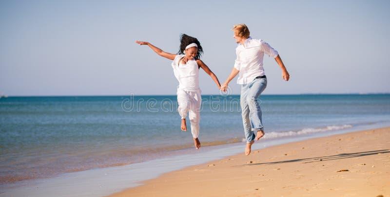 夫妇在海滩、黑人妇女和白人的假期 库存图片