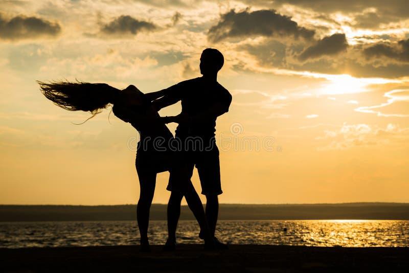 夫妇在海滩的剪影跳舞 免版税库存照片