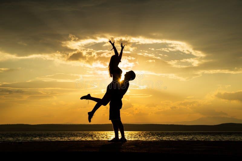 夫妇在海滩的剪影跳舞 库存照片