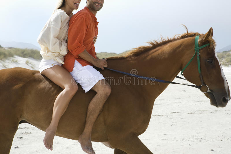 夫妇在海滩的骑乘马侧视图  免版税库存照片