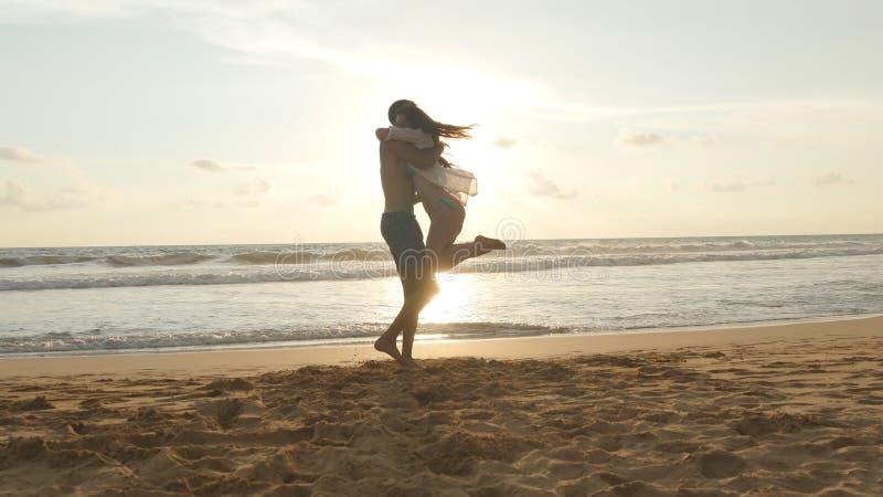 年轻夫妇在海滩,人拥抱跑并且转动他的日落的妇女 女孩跳进她的男朋友胳膊 免版税图库摄影