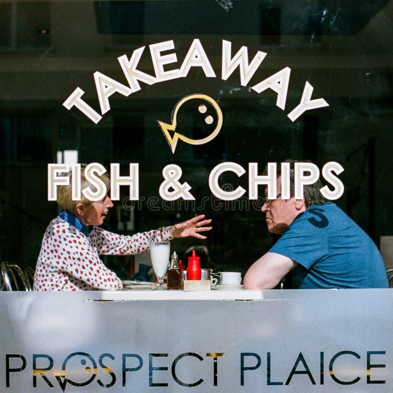 夫妇在炸鱼加炸土豆片商店,在德文郡,英国 免版税库存照片