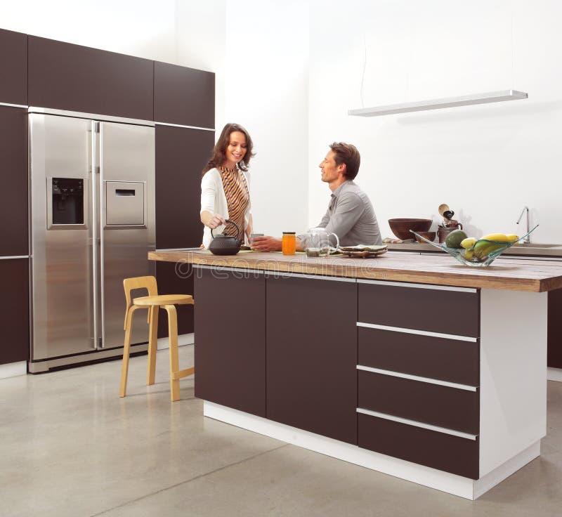 夫妇在现代厨房里 免版税库存图片