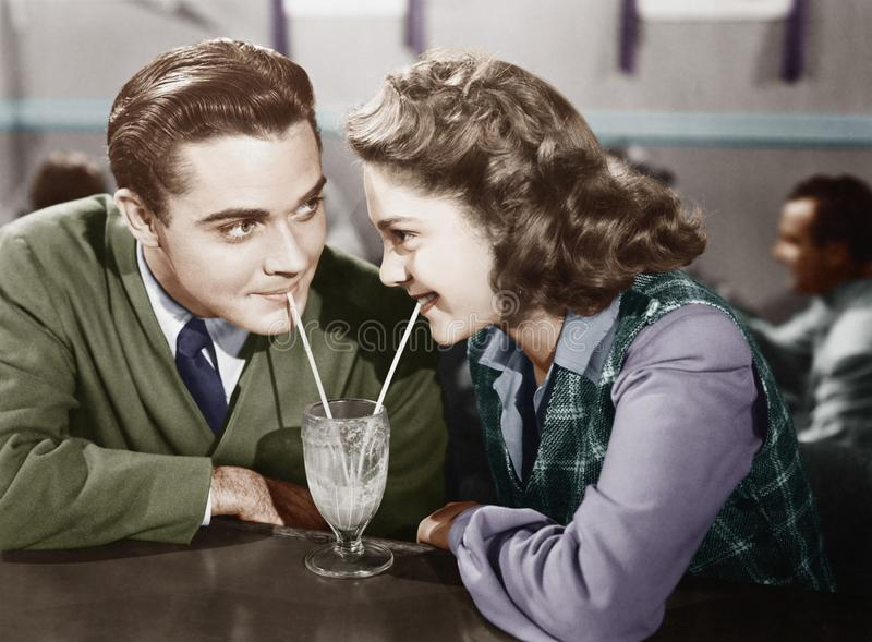 夫妇在看彼此和分享奶昔的餐馆与两秸杆(所有人被描述不是更长的生活 库存图片