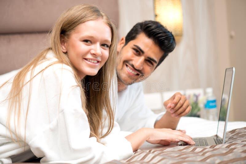 夫妇在研究膝上型计算机的床上 库存图片