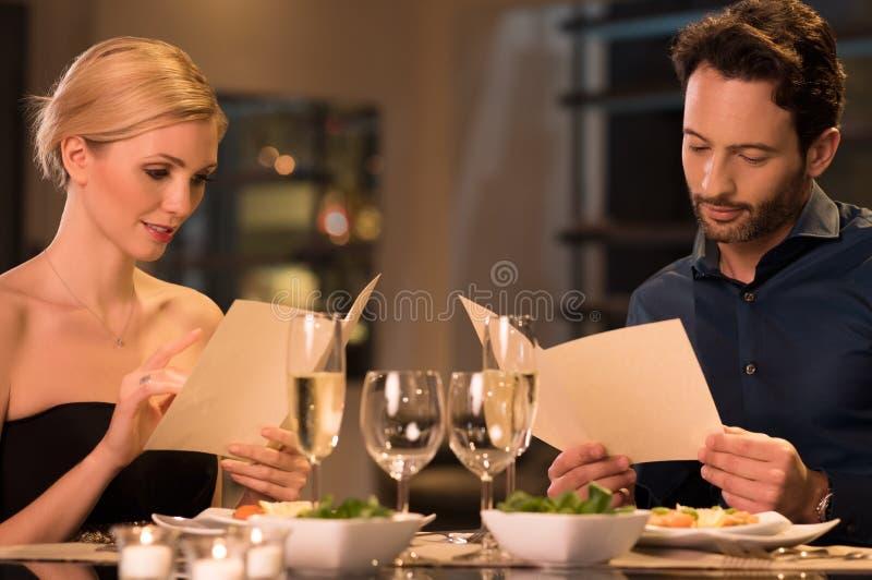 夫妇在餐馆的读书菜单 库存照片