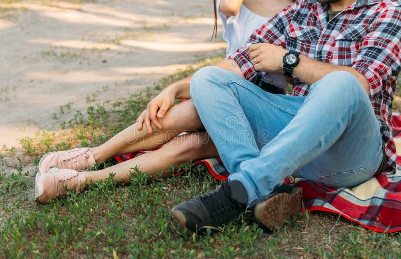 夫妇坐在一块沼地的红色格子花呢披肩有绿草的,暑假,周末,游人人有在他的胳膊的一块黑手表 免版税库存照片