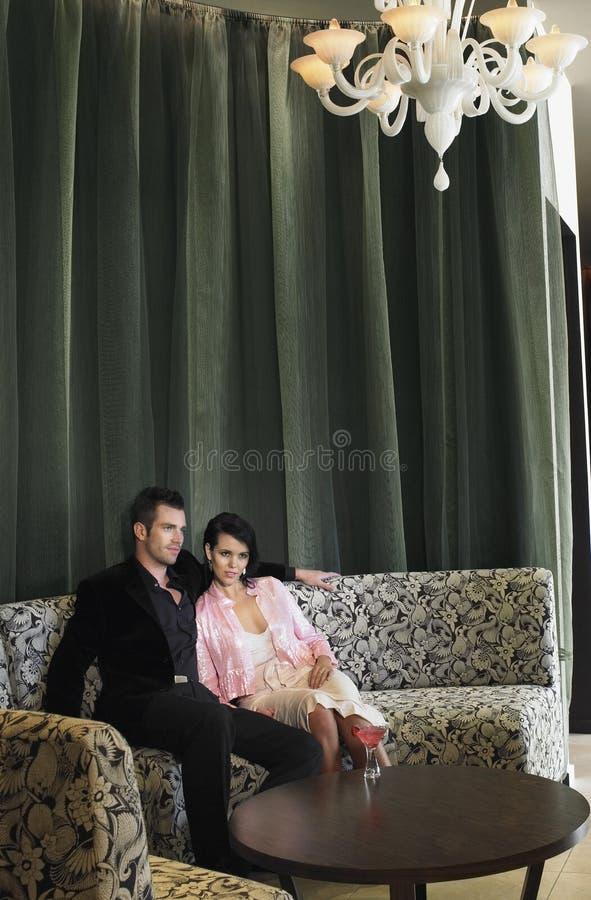 夫妇坐在旅馆大厅的长沙发 免版税图库摄影