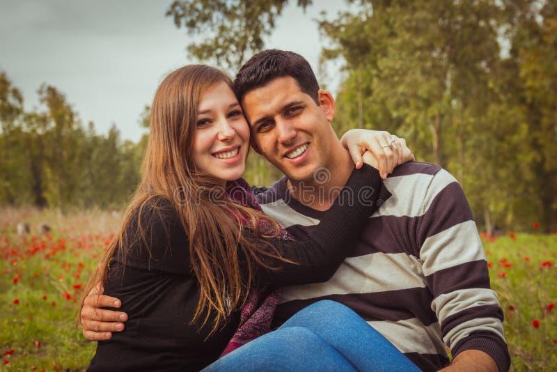 年轻夫妇坐在红色鸦片的领域的草和 免版税库存照片
