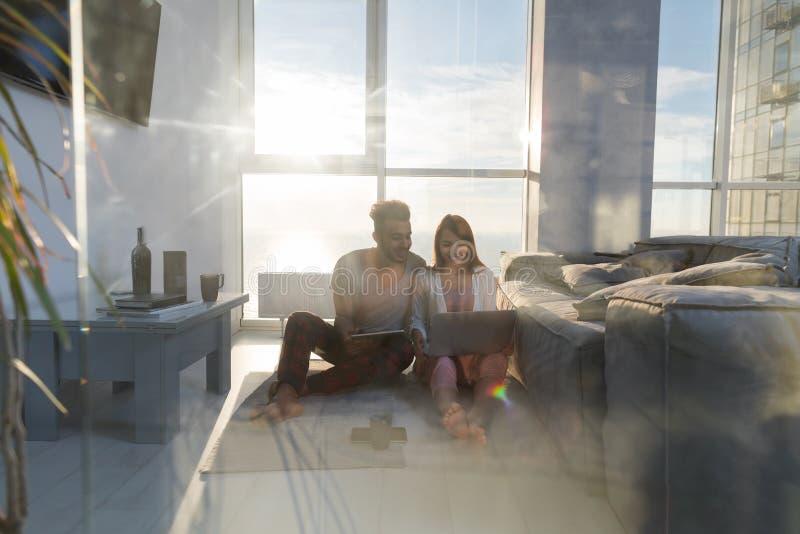 年轻夫妇坐地板使用膝上型计算机片剂计算机现代公寓大全景窗口海视图,混合种族人 图库摄影