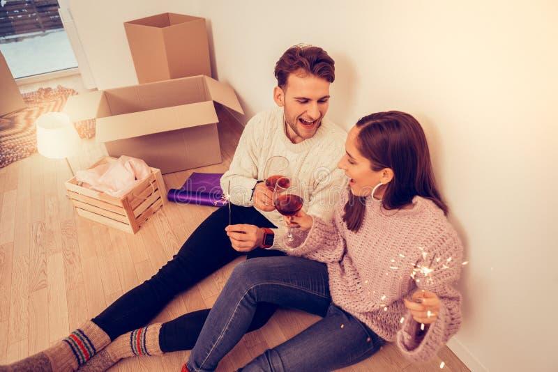 夫妇坐地板,当庆祝移动新的公寓时 库存图片