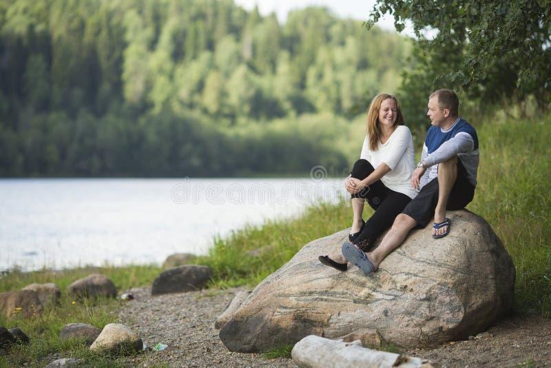 年轻夫妇坐岩石由河 免版税库存图片