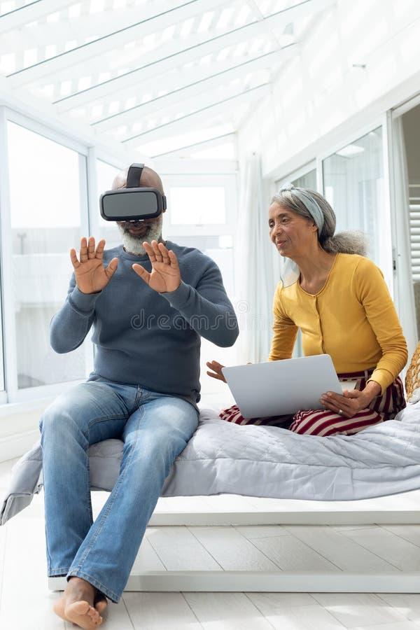 夫妇坐床,当使用数字设备时 免版税库存图片