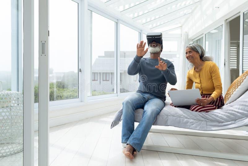 夫妇坐床,当使用数字设备时 库存图片