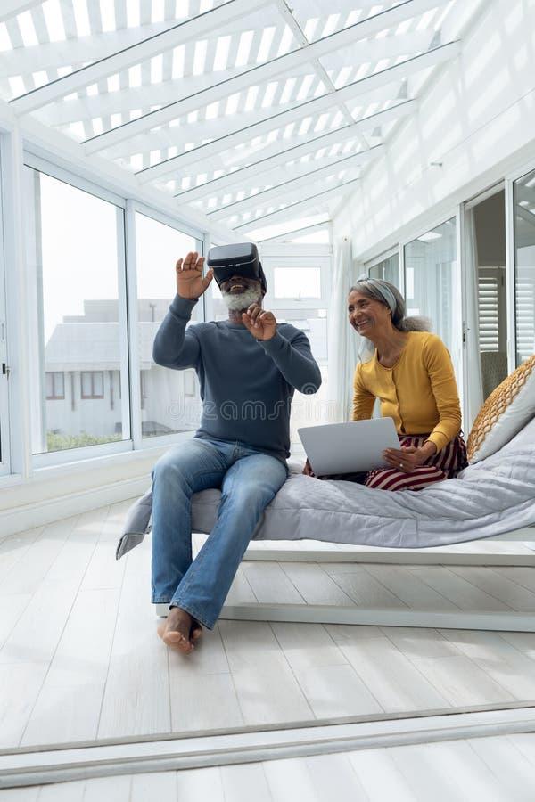 夫妇坐床,当使用数字设备时 免版税图库摄影