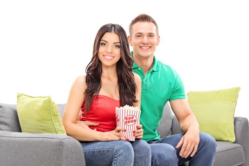 年轻夫妇坐有箱的长沙发玉米花 图库摄影