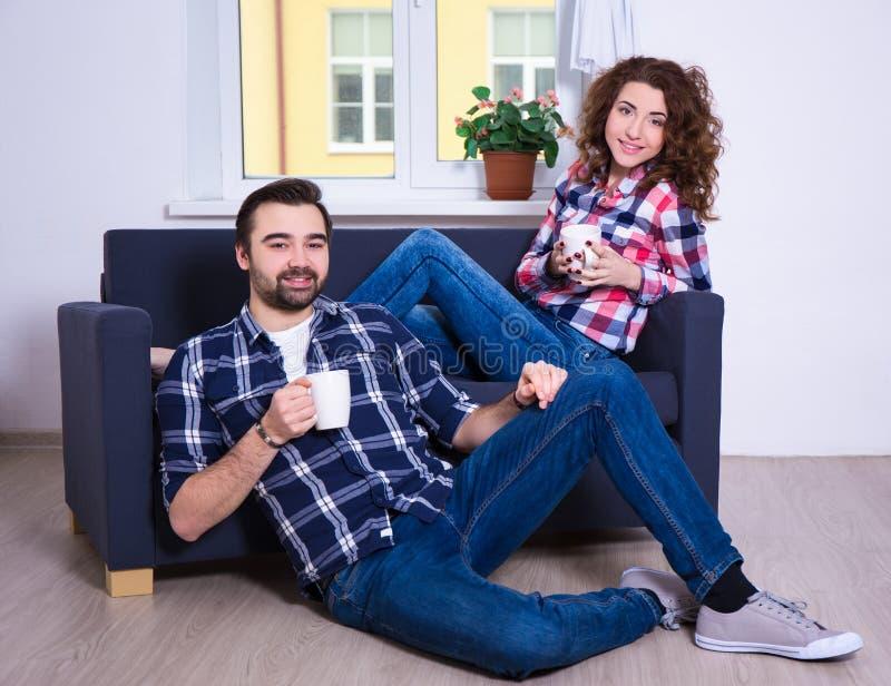 年轻夫妇坐有茶的沙发或咖啡在livin 库存照片