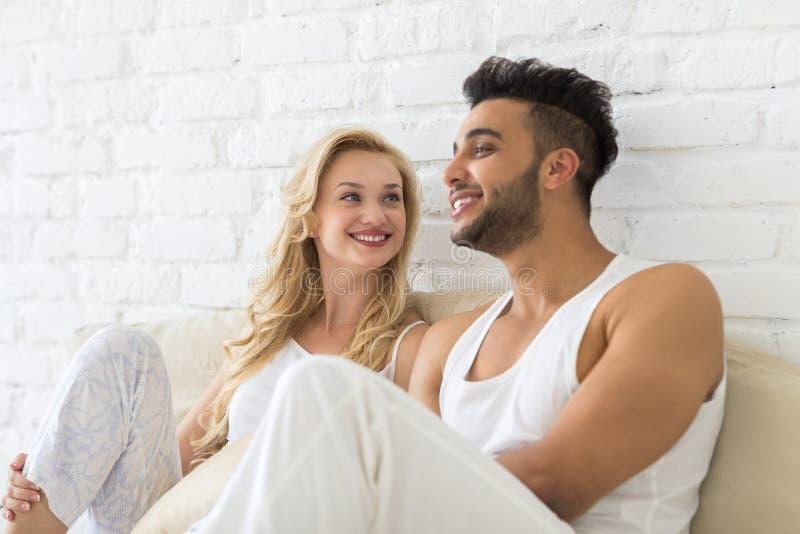 年轻夫妇坐枕头地板、愉快的微笑西班牙人和妇女恋人在卧室 免版税库存照片