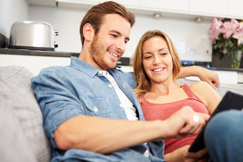 年轻夫妇坐沙发使用数字式片剂 免版税库存图片