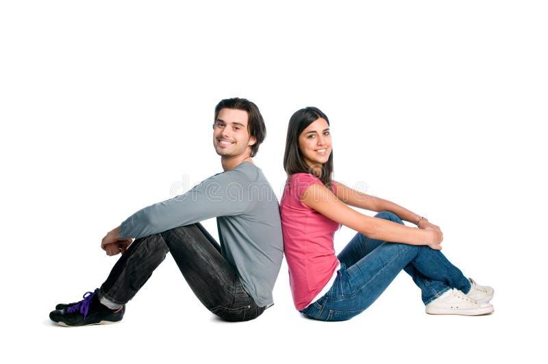 夫妇坐的一起微笑年轻人 免版税库存照片