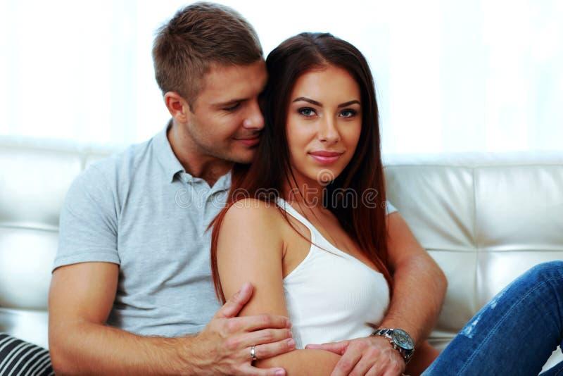 夫妇坐的沙发 免版税库存照片
