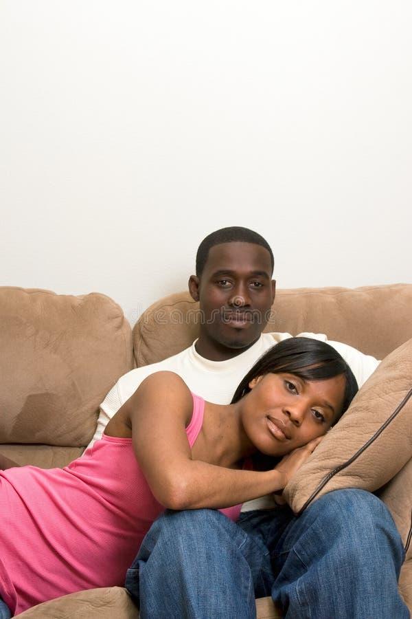 夫妇坐的沙发 免版税库存图片