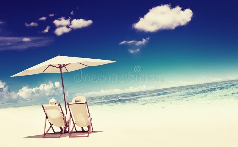 夫妇坐的海滩热带放松概念 库存照片