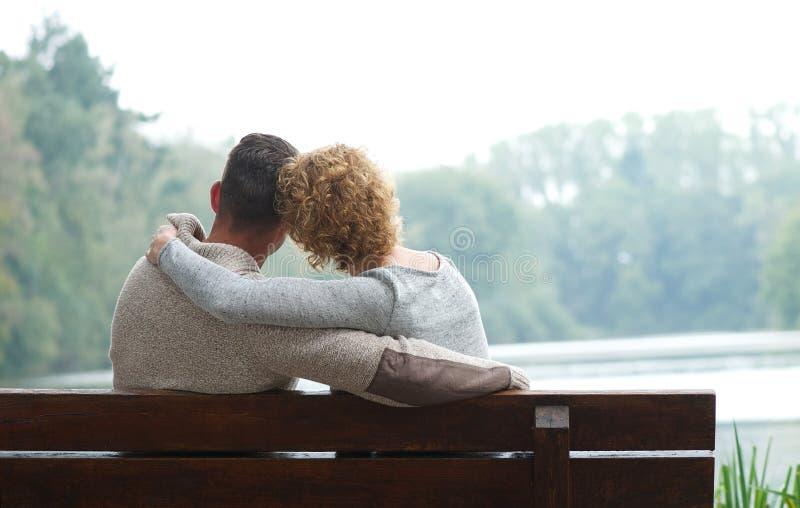 夫妇坐长凳由湖 图库摄影