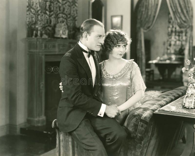 夫妇坐长沙发边缘  免版税图库摄影