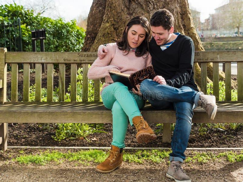 年轻夫妇坐读书的长凳 库存图片