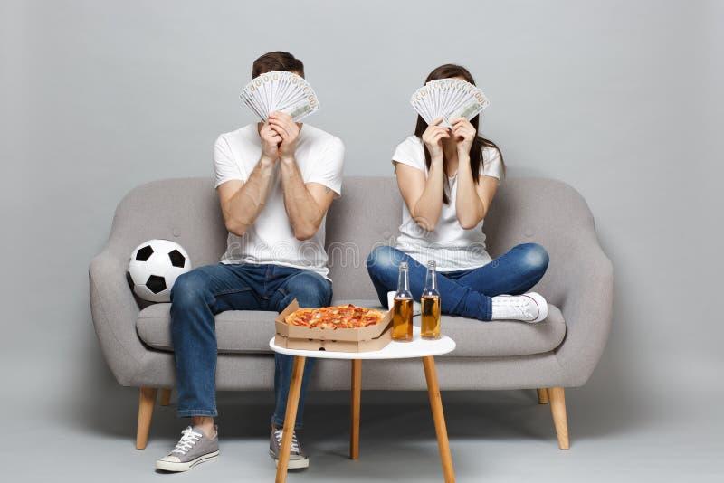 夫妇妇女人足球迷在美元钞票使支持喜爱的队振作,盖面孔用金钱爱好者,现金 免版税库存图片