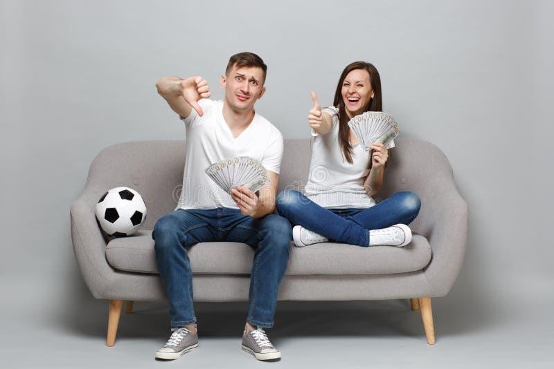 夫妇妇女人金钱支持喜爱的队藏品爱好者的足球迷欢呼在美元钞票现金金钱 免版税库存照片