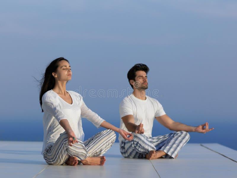 年轻夫妇实践的瑜伽 免版税图库摄影