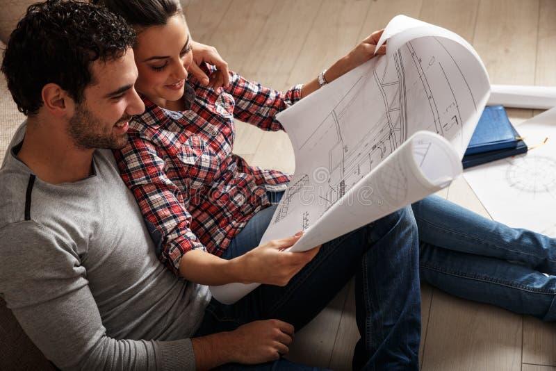 年轻夫妇审查的图纸 免版税库存图片