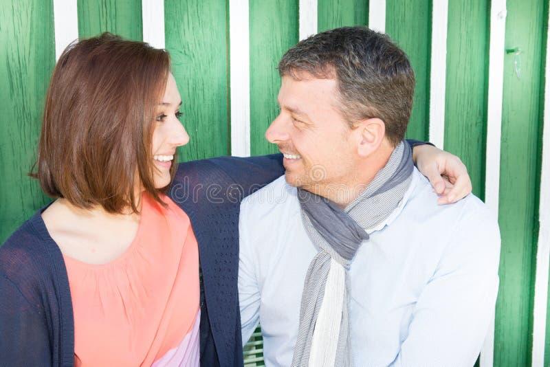 夫妇室外在晴天坐前面木小屋绿色和白色背景 免版税库存照片