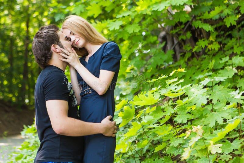 年轻夫妇室外画象 亲吻英俊的男孩的美丽的俏丽的女孩 肉欲的照片 免版税图库摄影
