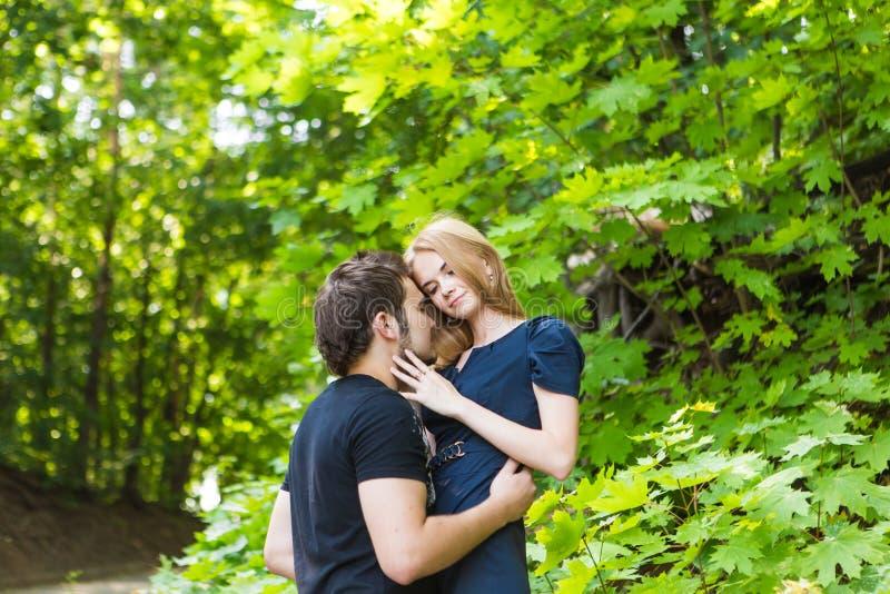 年轻夫妇室外画象 亲吻英俊的男孩的美丽的俏丽的女孩 肉欲的照片 免版税库存照片