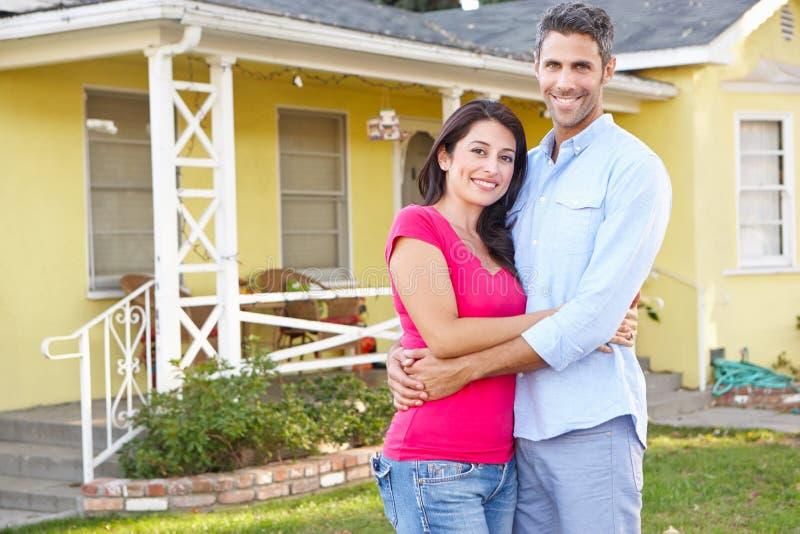 夫妇常设外部郊区家 免版税图库摄影