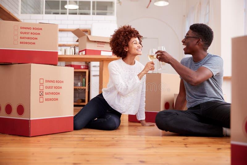 夫妇庆祝移动入新的家庭饮用的香宾 图库摄影