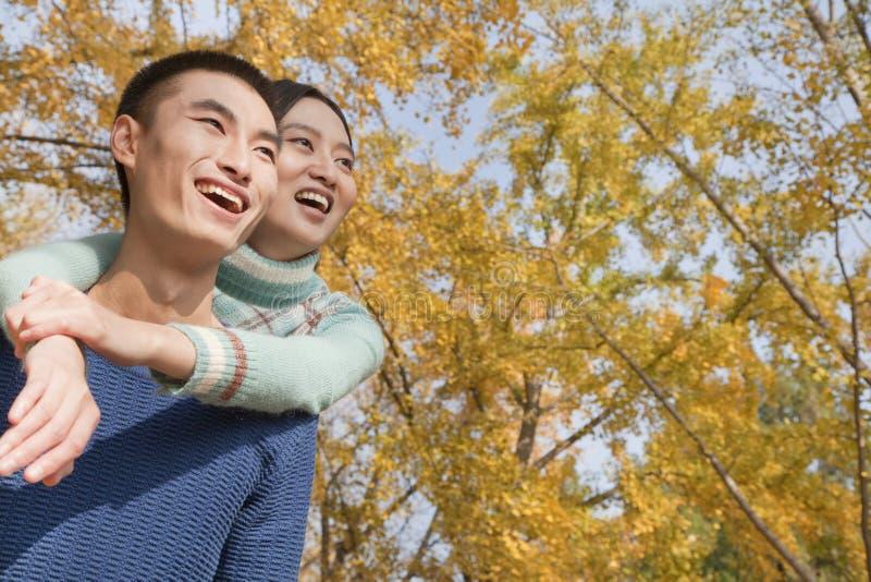 年轻夫妇微笑和肩扛在公园在秋天 图库摄影