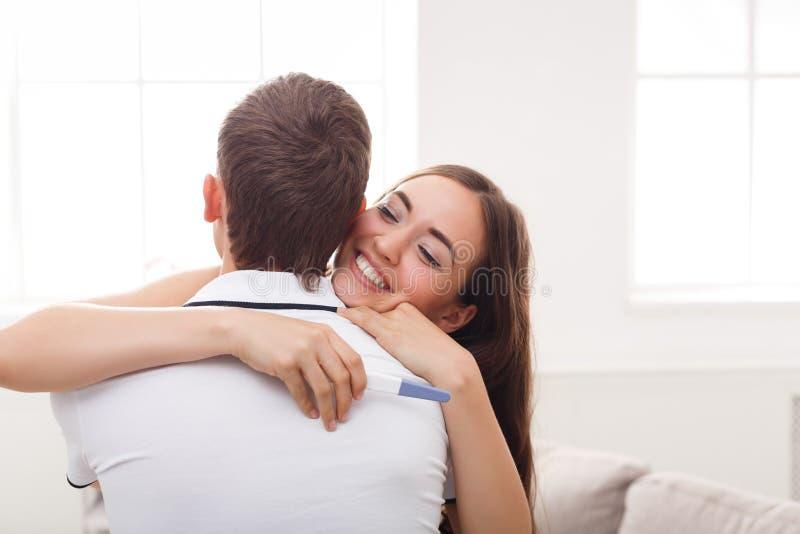 年轻夫妇愉快关于妊娠试验的结果 图库摄影