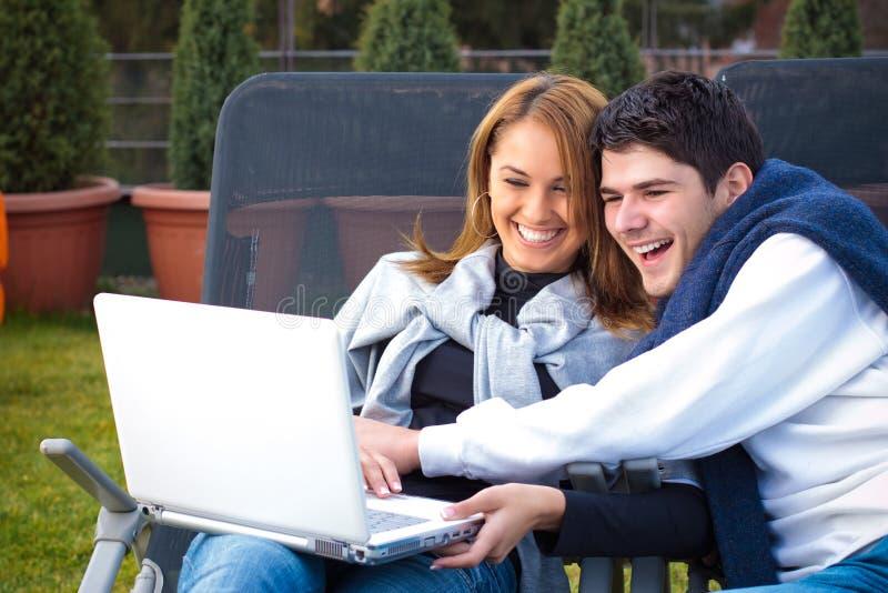 夫妇愉快的互联网冲浪年轻人 免版税库存照片